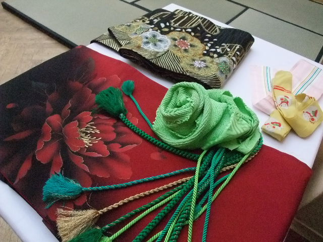 Kimono rosso, obi e accessori utilizzati durante la vestizione.