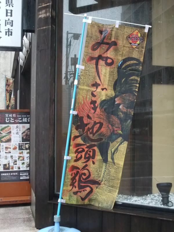 Sotto la pioggia, sventola lo stendardo del ristorante specializzato in pollo di Kyushu. Okayama, novembre 2015.